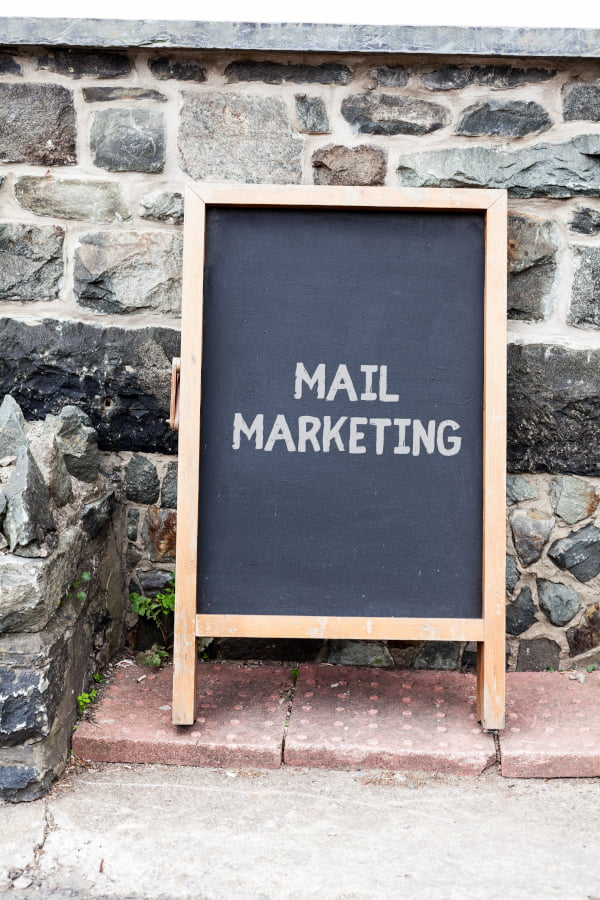 Sandwich Board with the words Mail Marketing written on it representing direct mail