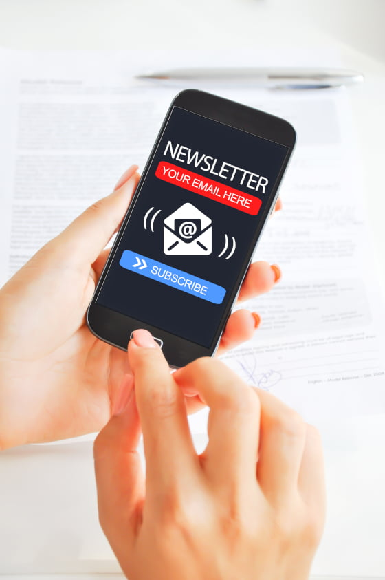 Image of hands holding a phone showing an electronic or e- Newsletter