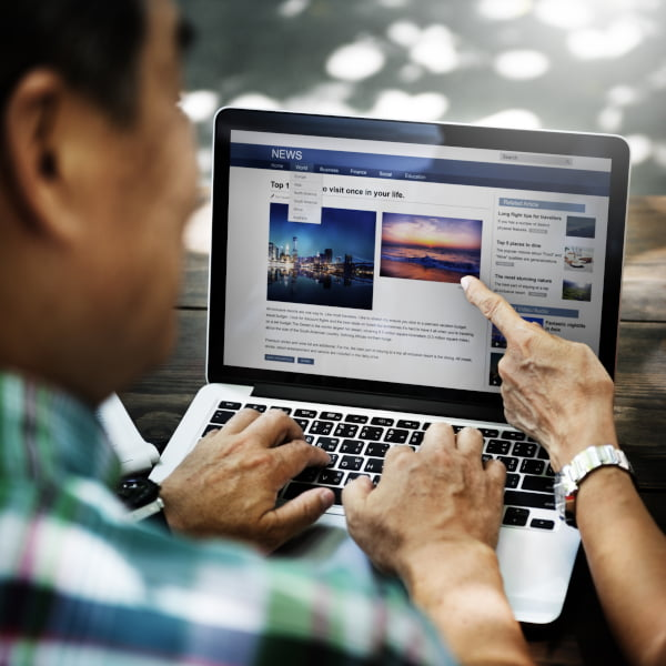 Image of a man and woman looking at a laptop with the woman pointing  out website news